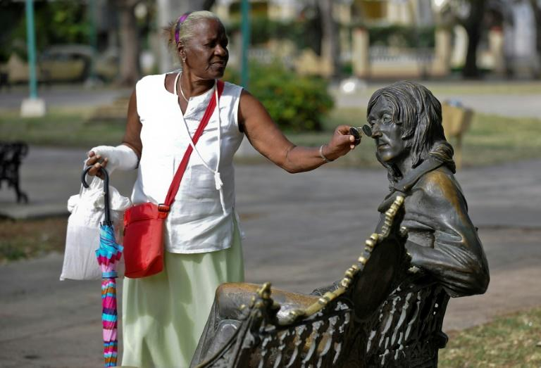 A woman puts glasses on a statue of John Lennon, in a park in Havana, on March 11, 2017