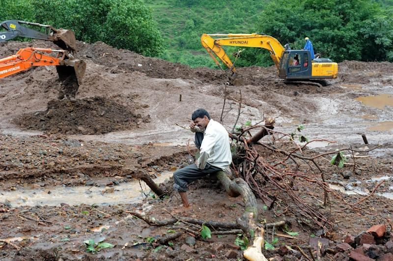 An Indian villager who lost 13 members of his family in a landslide, breaks down as he sits on an uprooted tree near the site of his former ancestral home in the western Indian state of Maharashtra on August 1, 2014