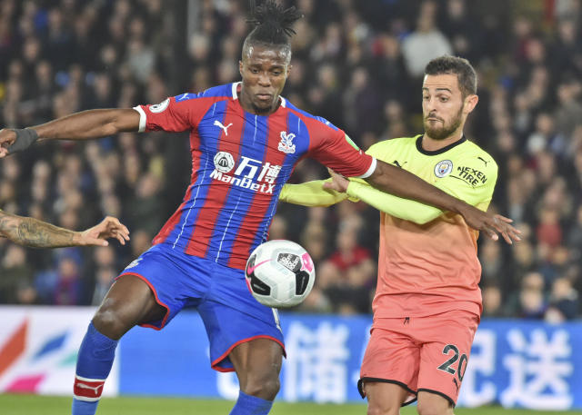 Crystal Palace's Wilfried Zaha, right, vies for the ball with Manchester City's Bernardo Silva during the English Premier League soccer match between Crystal Palace and Manchester City at Selhurst Park in London, England, Saturday, Oct. 19, 2019. (AP Photo/Rui Vieira)