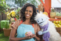 """This image released by Netflix shows former first lady Michelle Obama with Busy, a bee puppet, left, Mochi, a pink round puppet, and Waffles, a furry puppet with waffle ears on the set of the children's series """"Waffles + Mochi."""" Obama is launching the new Netflix children's food show on March 16. (Adam Rose/Netflix via AP)"""