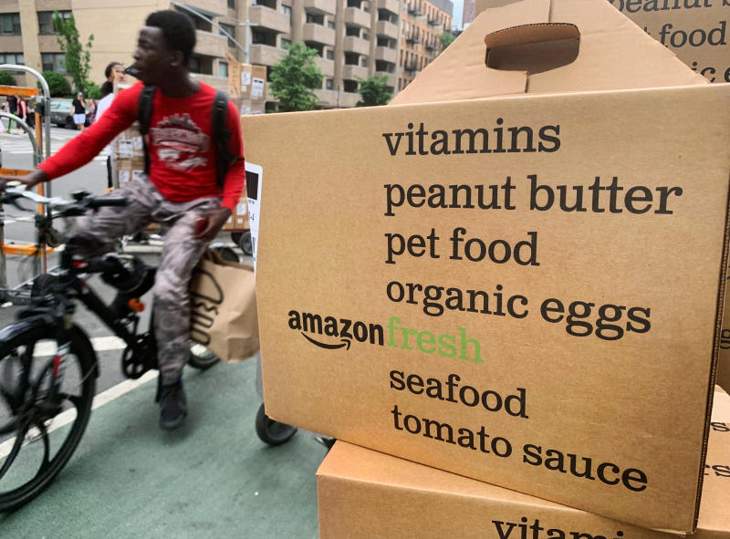 In this Sunday, June 16, 2019, a bike messenger rides past boxes of Amazon Fresh deliveries in New York. With the proliferation of subscription services, mobile payments and other conveniences, it's become easier for consumers to lose track of what they've signed up for and how much it's costing them. (AP Photo/Jenny Kane)