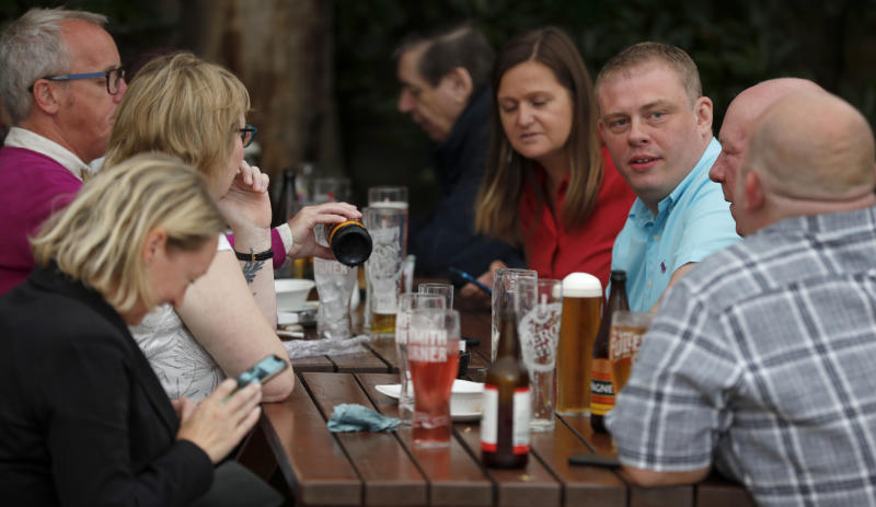 People enjoy their drinks at the beer garden of the Forester pub in London, Saturday, July 4, 2020. England is embarking on perhaps its biggest lockdown easing yet as pubs and restaurants have the right to reopen for the first time in more than three months. In addition to the reopening of much of the hospitality sector, couples can tie the knot once again, while many of those who have had enough of their lockdown hair can finally get a trim. (AP Photo/Frank Augstein)