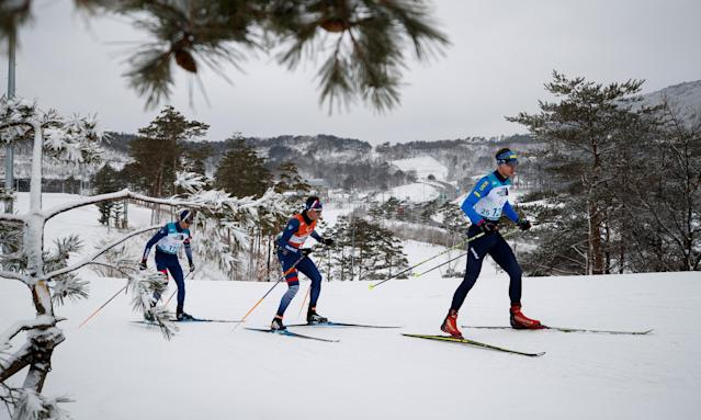 Iurii Utkin of Ukraine is seen in front of Anthony Chalencon of France and his guide Simon Valverde as they compete in the Biathlon Visually Impaired Men's 15km