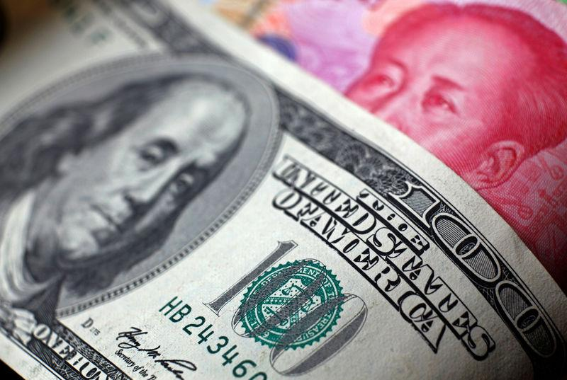 FILE PHOTO: A Chinese 100 yuan banknote is placed under a $100 banknote (top) in this photo illustration taken in Beijing in this November 7, 2010 file photo. REUTERS/Petar Kujundzic/File Photo