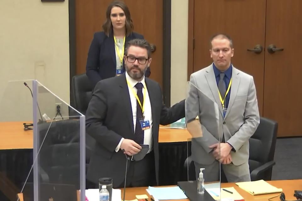 In this screen grab from video, defense attorney Eric Nelson, left, defendant and former Minneapolis police officer Derek Chauvin, right, and Nelson's assistant Amy Voss, back, introduce themselves to jurors as Hennepin County Judge Peter Cahill presides over jury selection in the trial of Chauvin Wednesday, March 17, 2021 at the Hennepin County Courthouse in Minneapolis, Minn. Chauvin is charged in the May 25, 2020 death of George Floyd. (Court TV, via AP, Pool)