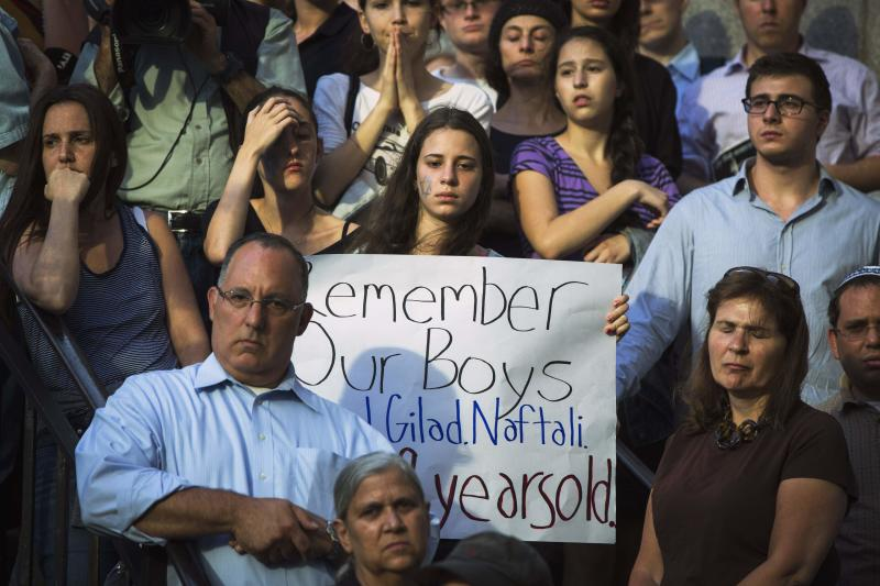 A woman holds a sign during a memorial service for three missing Israeli teenagers whose bodies were found in the occupied West Bank, near the United Nations headquarters in New York, June 30, 2014. Several hundred people waving Israeli flags and expressing grief and solidarity held a vigil in New York on Monday after the bodies of Eyal Yifrach, 19, Gilad Shaar, 16, and Naftali Fraenkel, 16, were found in a field near Hebron, a militant stronghold, not far from a road where they were believed to have been abducted while hitchhiking on June 12, security officials said. REUTERS/Lucas Jackson (UNITED STATES - Tags: POLITICS CIVIL UNREST)