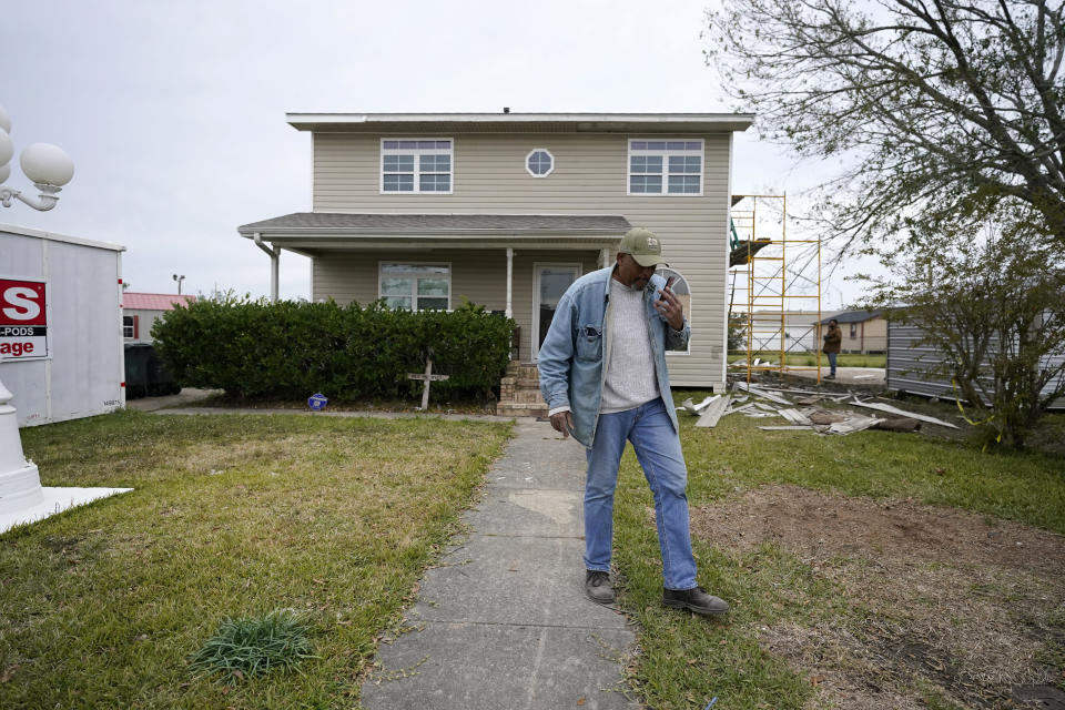CORRECTS FIRST NAME TO WILFRED - Wilfred Trahan talks on his phone while workers repair siding on his damaged home, in the aftermath of both Hurricane Laura and Hurricane Delta, in Lake Charles, La., Friday, Dec. 4, 2020. (AP Photo/Gerald Herbert)