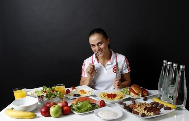 Turkish wrestler and Olympic hopeful Elif Jale Yesilirmak, 26, poses in front of her daily meal intake in Ankara May 29, 2012.