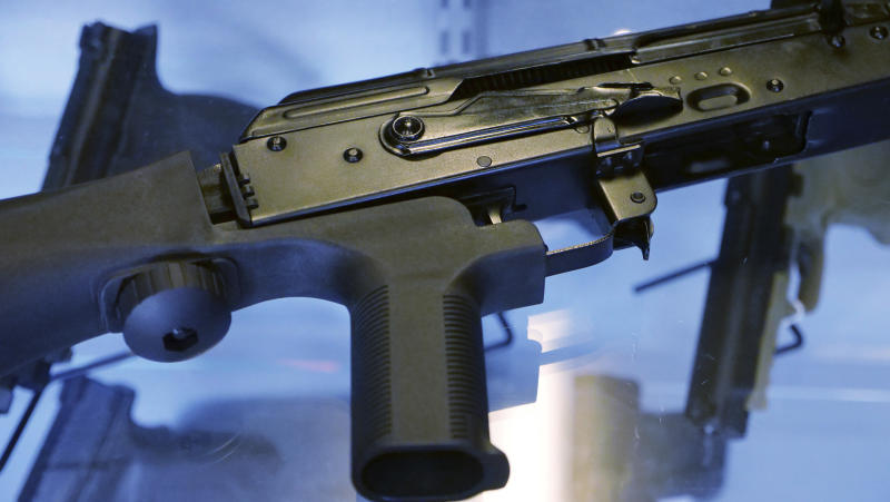 """In this Oct. 4, 2017, photo, a device called a """"bump stock"""" is attached to a semi-automatic rifle at the Gun Vault store and shooting range in South Jordan, Utah. The slaying of five dozen people at a Las Vegas music festival did little to change American opinion about the nation's gun laws, and the country is divided over whether restricting firearms would reduce the number of such mass shootings or homicides, according to a new poll from The Associated Press-NORC Center for Public Affairs Research. (AP Photo/Rick Bowmer)"""