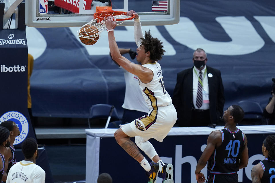 New Orleans Pelicans center Jaxson Hayes (10) slam dunks over Sacramento Kings forward Harrison Barnes (40) in the first half of an NBA basketball game in New Orleans, Monday, April 12, 2021. (AP Photo/Gerald Herbert)