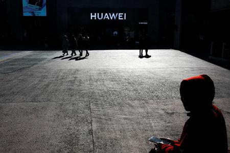 A man uses his phone as he sits in front of a Huawei shop in Beijing