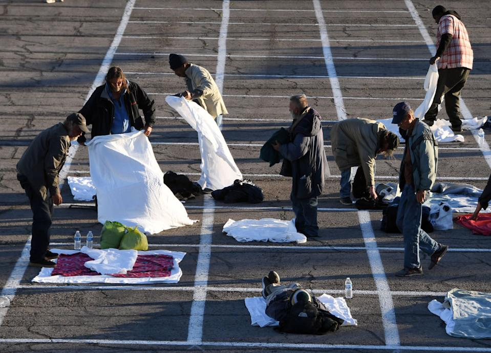 Homeless people lay out blankets in a parking lot at Cashman Center in Las Vegas, Nevada.