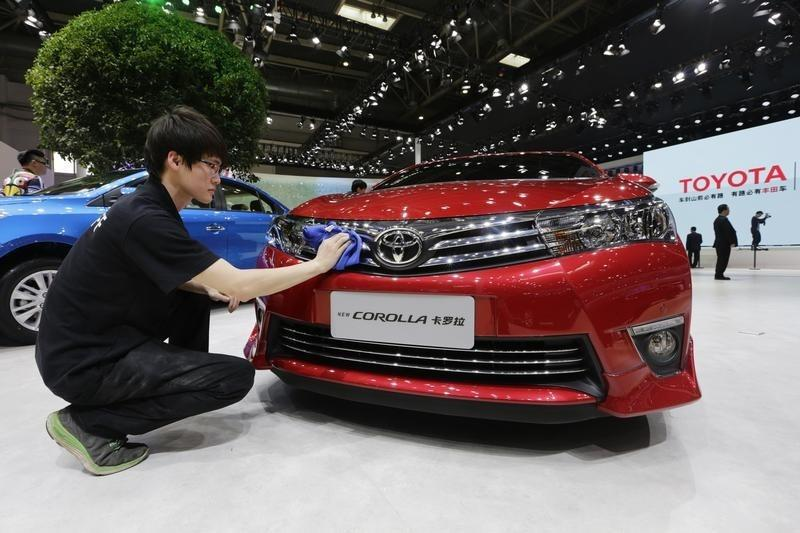 A man cleans a new Toyota COROLLA car at Auto China 2014 in Beijing