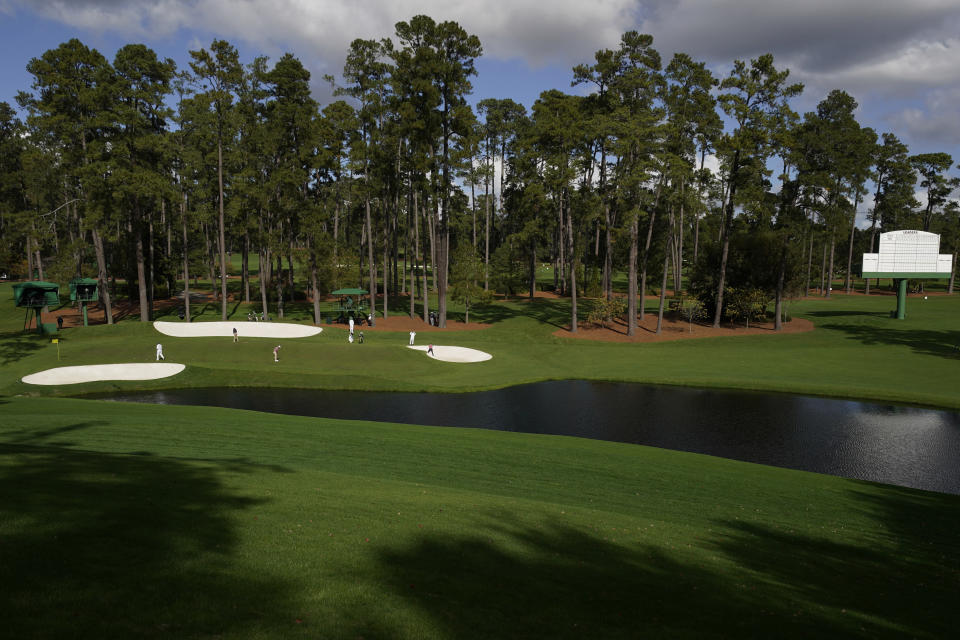 With no spectators on the course, the group of Tommy Fleetwood, of England, Justin Rose, of England, and Collin Morikawa play the 16th hole during a practice round for the Masters golf tournament Monday, Nov. 9, 2020, in Augusta, Ga. (AP Photo/Charlie Riedel)