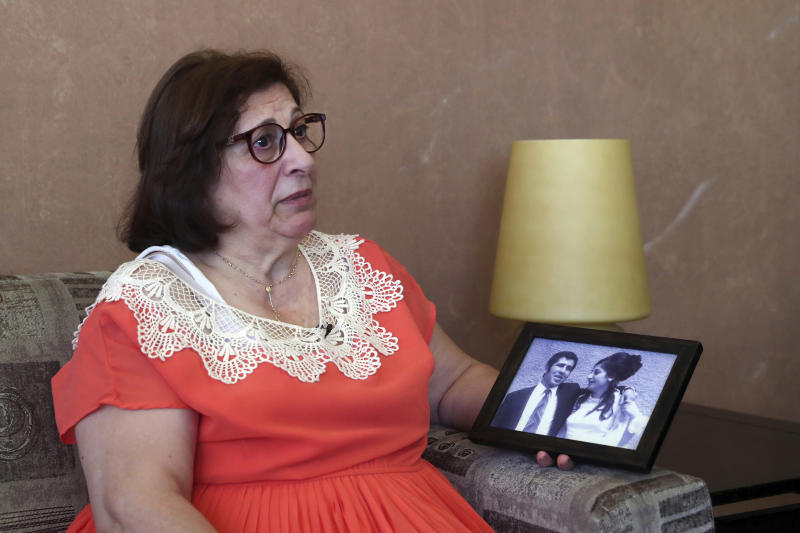 Laure Ghosn, whose husband Charbel Zogheib has been missing for the past 37 years, speaks as she holds their wedding portrait during an interview at her home in Sarba, north of Beirut, Lebanon. Ghosn said her husband is held in Syria and hopes that a new wave of sanctions imposed by the U.S. against the Syrian government will force Damascus to reveal the fate of hundreds of Lebanese citizens held in Syria, including that of her husband. (AP Photo/Bilal Hussein)