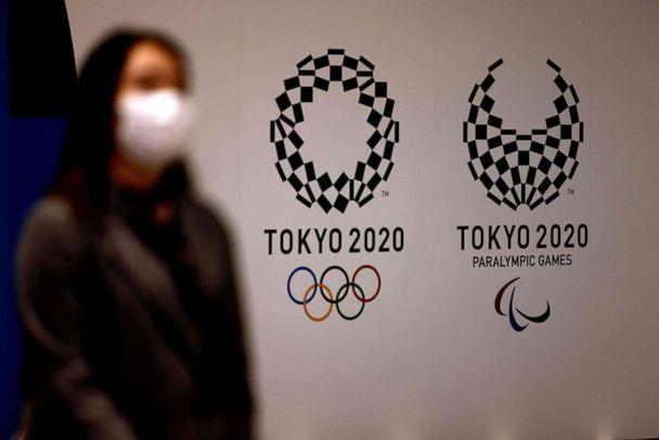PHOTO: A woman wearing a face mask to protect against the novel coronavirus walks past logos of Tokyo 2020 Olympic and Paralympic Games in Tokyo, Japan, on Feb. 2, 2021. (Behrouz Mehri/AFP via Getty Images)