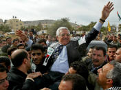 """FILE - In this Dec. 30, 2004 file photo, then Interim Palestinian leader Mahmoud Abbas, and front-runner in the upcoming presidential elections, is carried by the Al Aqsa Martyrs' Brigades leader in West Bank, Zakaria Zubeidi, center left, during a campaign visit to the Jenin refugee camp. For nearly two decades, Zubeidi has been an object of fascination for Israelis and Palestinians alike, who have seen his progression from a child actor to a swaggering militant, to the scarred face of a West Bank theater promoting """"cultural resistance"""" to Israeli occupation. In his latest act, he has emerged as one of Israel's most wanted fugitives after tunneling out of a high-security prison on Monday, Sept. 6, 2021 with five other Palestinian militants. (AP Photo/Enric Marti, File)"""