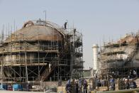 FILE- In this Sept. 20, 2019 file photo taken during a trip organized by Saudi information ministry, workers fix the damage in Aramco's oil separator at processing facility after the recent Sept. 14 attack in Abqaiq, near Dammam in the Kingdom's Eastern Province. Yemen's war began in September 2014, when the Houthis seized the capital Sanaa. Saudi Arabia, along with the United Arab Emirates and other countries, entered the war alongside Yemen's internationally recognized government in March 2015. The war has killed some 130,000 people and driven the Arab world's poorest country to the brink of famine. (AP Photo/Amr Nabil, File)