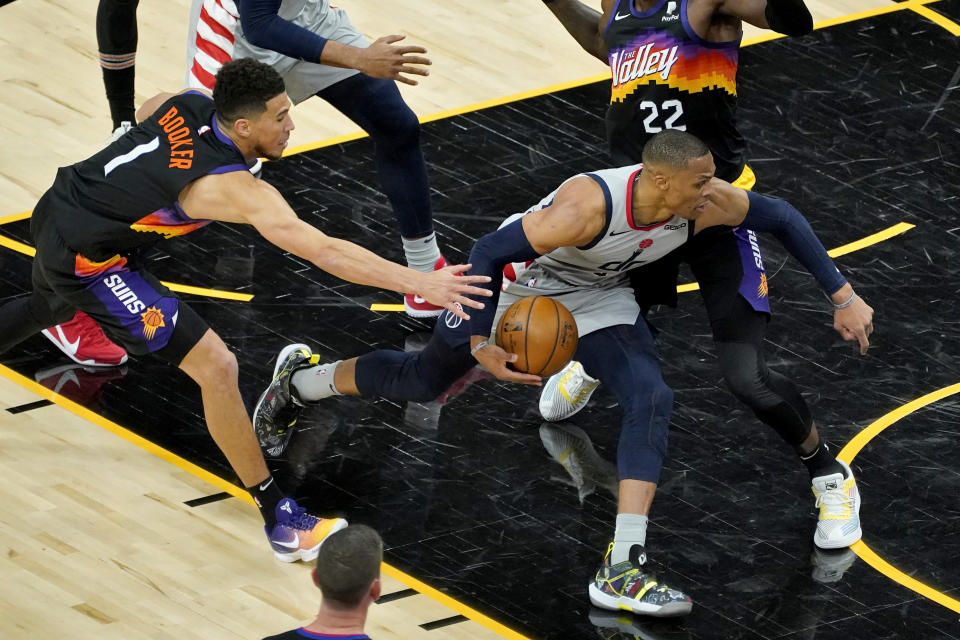 Washington Wizards guard Russell Westbrook drives on Phoenix Suns center Deandre Ayton (22) during the second half of an NBA basketball game, Saturday, April 10, 2021, in Phoenix. (AP Photo/Matt York)