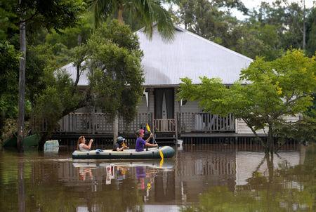 Locals float past a house in a boat on a flooded street in the northern New South Wales town of Lismore, Australia, after heavy rains associated with Cyclone Debbie swelled rivers to record heights across the region