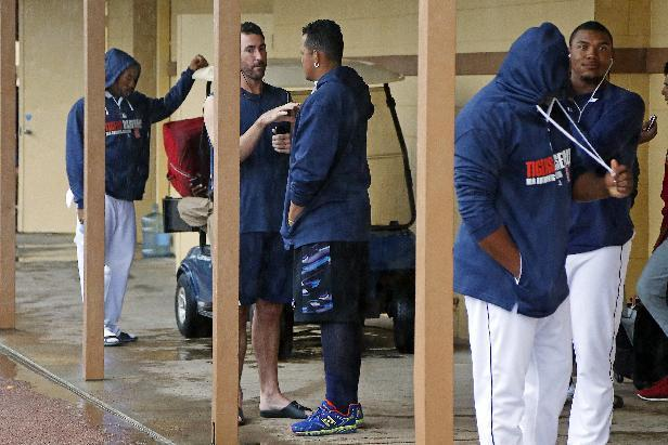 Detroit Tigers' Justin Verlander, center left, talks with Miguel Cabrera, center right, as Tigers players gather outside their locker room while waiting for an exhibition spring training baseball game between the Tigers and the Philadelphia Phillies to be called due to rain in Lakeland, Fla., Thursday, March 6, 2014. (AP Photo/Gene J. Puskar)
