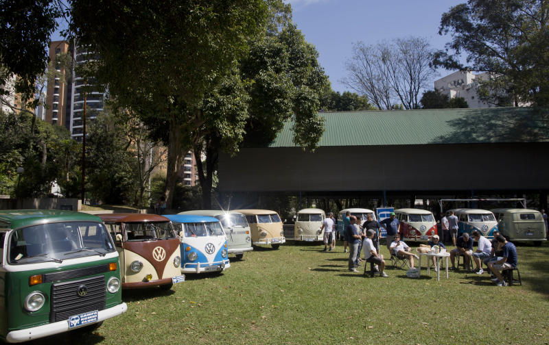 "In this Aug. 25, 2013 photo, members of the Sampa Kombi club, a group ofVolkswagen van owners, gather for their monthly meeting, in Sao Paulo, Brazil. In Brazil the VW van is known as the ""Kombi,"" an abbreviation for the German ""Kombinationsfahrzeug"" that loosely translates as ""cargo-passenger van."" Brazil is the last place in the world still producing the iconic vehicle, or ""bus"" as it's known by aficionados, but VW says production will end Dec. 31. Safety regulations mandate that every vehicle in Brazil must have air bags and automatic brakes starting in 2014, and the company says it cannot change production to meet the law. (AP Photo/Andre Penner)"