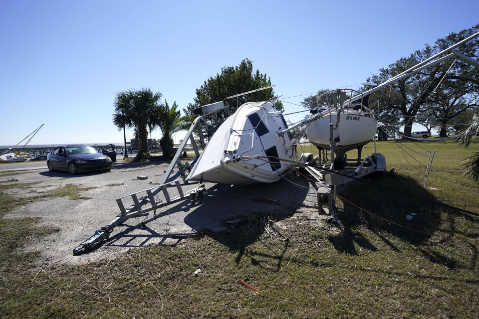 A sailboat on a trailer sits overturned in Pass Christian, Miss., Thursday, Oct. 29, 2020, in the aftermath of Hurricane Zeta, which passed through Wednesday . (AP Photo/Gerald Herbert)