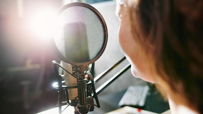 Shot of a woman speaking into a microphone in a recording studio.