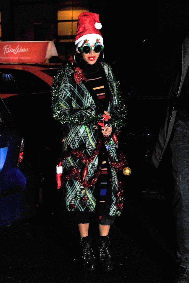 <p>And the coolest girl-boss award goes to….Beyoncé! For her company's holiday party, Bey dressed up as a Christmas tree IRL. Layered over a striped sweater dress that she paired with combat boots, B wore a calf-length green and black sweater adorned with lights, tinsel and ornaments. Her outfit was made even more jolly with a Santa hat and kitschy Christmas tree sunglasses. Tis the season! (Photo: Getty Images)</p>