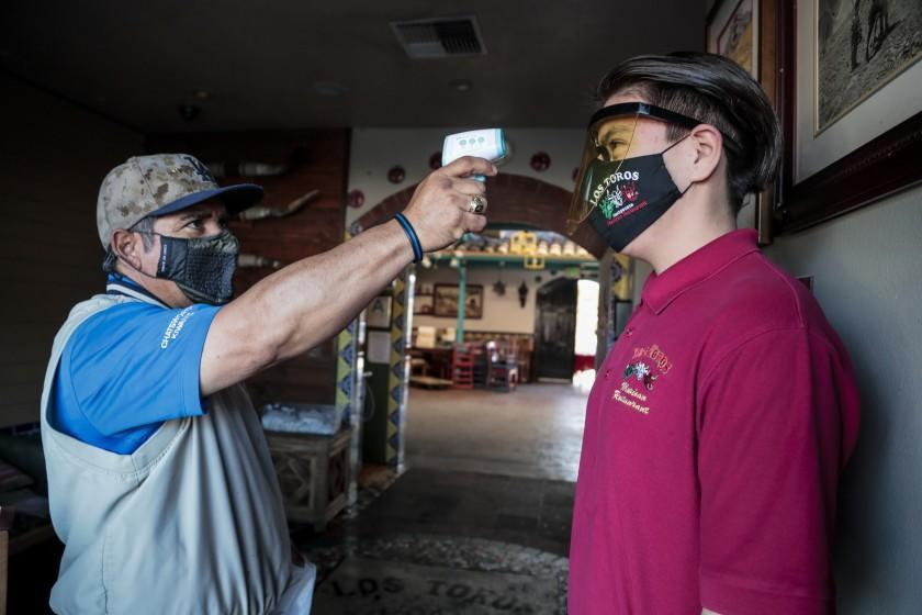 Chatsworth, CA, Saturday, February 27, 2021 - Diego Almendor has his temperature read by Los Toros Mexican restaurant owner Nicolas Montano as he arrives begins his shift. The restaurant has been closed for indoor dining since March, due to COVID-19. It is now open for takeout and outdoor dining. Montano says a measure pending in the CA legislature to require businesses to offer employees 2 weeks of mandatory paid sick leave for COVID-19 related absences would be devastating to small businesses. He is avoiding having to pay sick leave by taking the temperature of all his workers before every shift. (Robert Gauthier/Los Angeles Times)