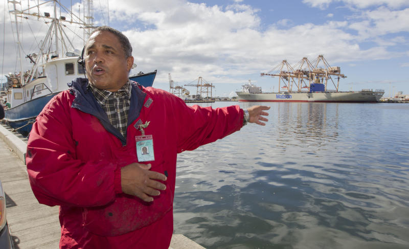 John Hernandez of Kailua, Hawaii and owner of John's Fresh Fish, gestures as he describes the effect of the spilled molasses will have on the marine like in Honolulu Harbor and near by Keehi Lagoon Thursday, Sept. 12, 2013, in Honolulu. Off to the right in the back ground is the Matson container ship Mahi Mahi which is being loaded at the Matson container base yard's pier 52. A pipe maintained by Matson at pier 52 cracked and leaked about 233,000 gallons of molasses into the harbor. The molasses spill is being blamed for the killing of marine life at Keehi Lagoon which is located near the Honolulu Harbor. The cracked pipe has been repaired and the molasses leak stopped. (AP Photo/Eugene Tanner)