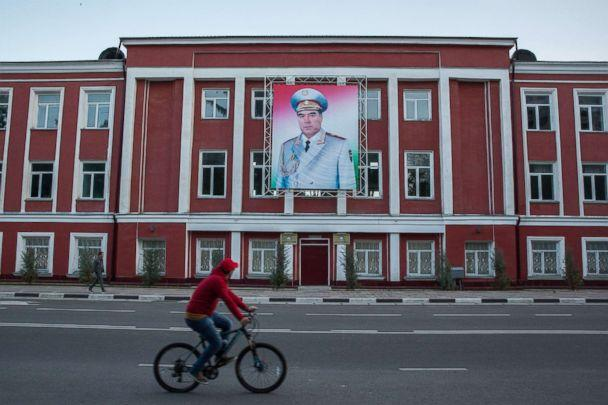 PHOTO: A cyclist rides past a banner featuring an image of Tajikistan President Emomali Rahmon displayed on a building in Dushanbe, Tajikistan, on April 22, 2018. (Taylor Weidman/Bloomberg via Getty Images)