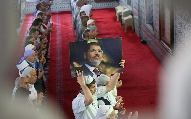 A man holds up an image of former Egyptian President Mohamed Morsi during a funeral prayer in absentia - Anadolu