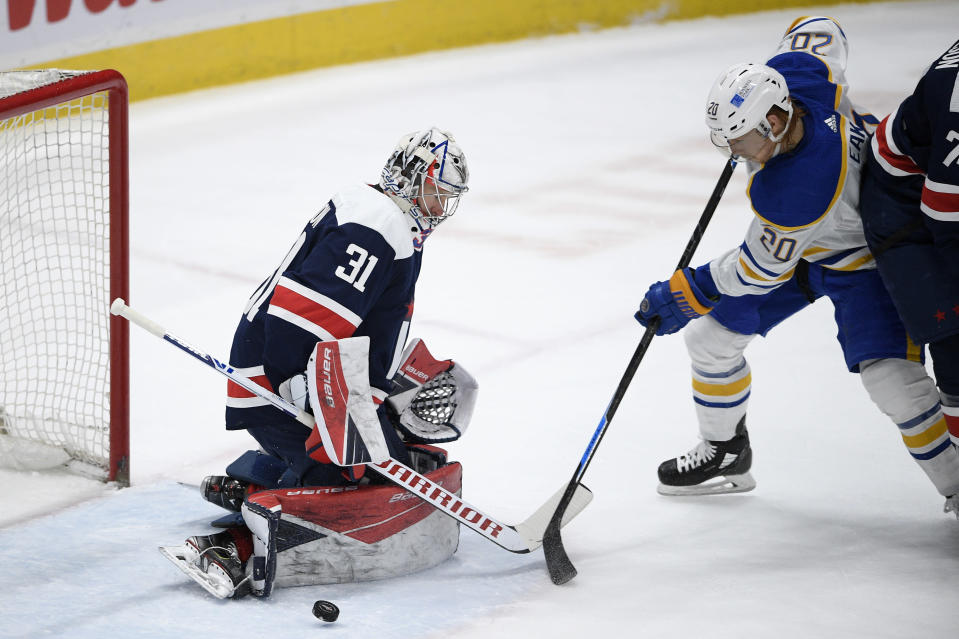 Buffalo Sabres center Cody Eakin (20) works for the puck in front of Washington Capitals goaltender Craig Anderson (31) during the second period of an NHL hockey game Thursday, April 15, 2021, in Washington. (AP Photo/Nick Wass)