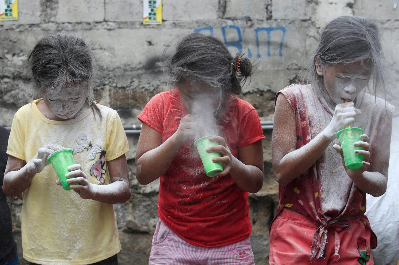 Girls' faces are covered by white powder after blowing it, at a town fiesta parlour game, in celebration of patron saint Santa Rita de Cascia in Baclaran, Paranaque City, Metro Manila, Philippines May 20, 2018. REUTERS/Romeo Ranoco     TPX IMAGES OF THE DAY