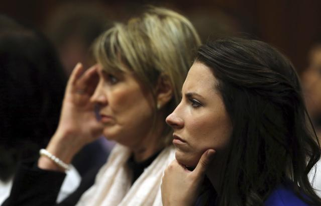 Oscar Pistorius' sister Aimee (R) listens as Pistorius speaks in the North Gauteng High Court in Pretoria April 11, 2014. Pistorius is on trial for murdering his girlfriend Reeva Steenkamp at his suburban Pretoria home on Valentine's Day last year. REUTERS/Themba Hadebe/Pool (SOUTH AFRICA - Tags: SPORT ATHLETICS CRIME LAW)