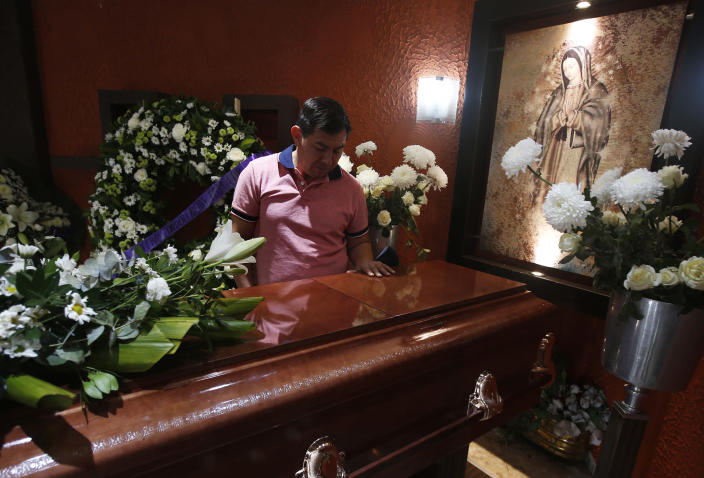 Jesus Sanchez places his hand on the casket containing the remains of his wife Liliana Lopez, 37, who died in the Mexico City Metro collapse disaster, during a wake in Mexico City, Wednesday, May 5, 2021. Monday night's accident was one of the deadliest in the history of the capital's subway system. (AP Photo/Marco Ugarte)