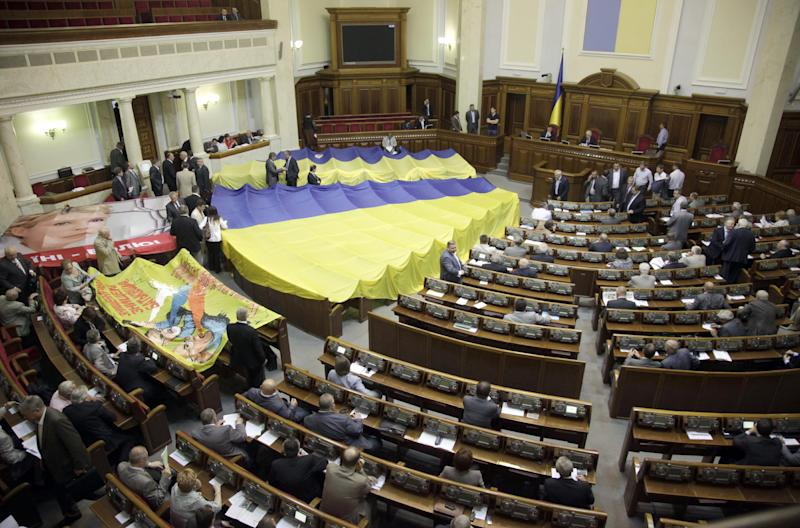 A large Ukrainian flag covered the seats of oppositions lawmakers after a vote on a bill of language in the Ukrainian parliament in Kiev, Ukraine, Tuesday, June 5, 2012. Ukraine's parliament has given tentative approval to a hotly contested bill that would allow the use of the Russian language alongside Ukrainian in some regions. Defying vehement protests by the opposition, pro-government lawmakers passed the bill in the first of two readings Tuesday. (AP Photo/Efrem Lukatsky)