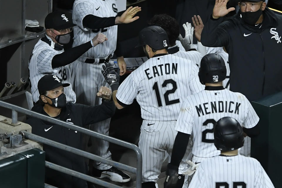 Chicago White Sox's Adam Eaton (12) celebrates with manager Tony La Russa left, at the dugout after hitting a three-run home run during the third inning of a baseball game against the Cleveland Indians Monday, April 12, 2021, in Chicago. (AP Photo/Paul Beaty)
