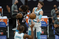 Charlotte Hornets guard LaMelo Ball (2) passes the ball around Sacramento Kings center Richaun Holmes (22) to teammate Bismack Biyombo during the first quarter of an NBA basketball game in Sacramento, Calif., Sunday, Feb. 28, 2021. (AP Photo/Randall Benton)