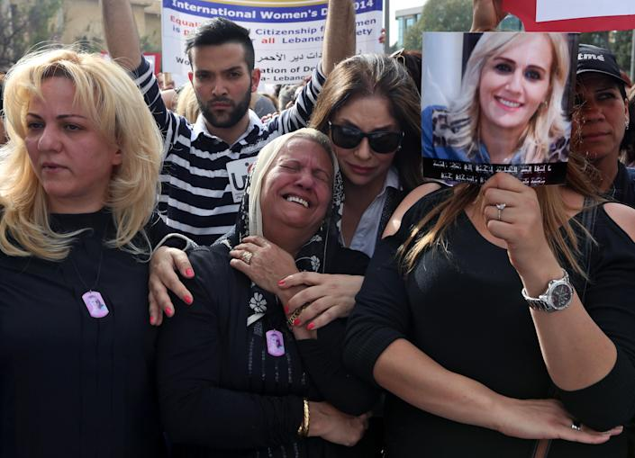 Nada Sabbagh, center, whose daughter was killed by her son-in-law weeps while taking part in a rally making International Woman's Day demanding that parliament approves a law that protects women from domestic violence in Beirut, Lebanon, Saturday, March 8, 2014. The killing of Sabbagh's daughter is one of three domestic violence slayings in Lebanon in recent months, drawing new attention to women's rights in this country of 4 million people. Although Lebanon appears very progressive on women rights compared to other countries in the Middle East, domestic violence remains an unspoken problem and the nation's parliament has yet to vote on a bill protecting women's rights nearly three years after it was approved by the Cabinet. (AP Photo/Bilal Hussein)