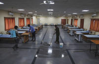 Indian workers disinfectant an isolation center for COVID-19 positive people in Hyderabad, India, Monday, May 3, 2021. (AP Photo/Mahesh Kumar A.)