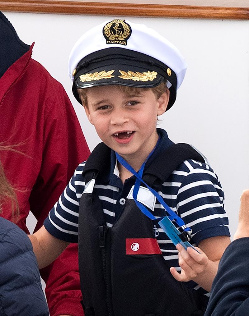 Prince George, with missing front teeth and wearing a Captain's cap, watches the inaugural King's Cup regatta, hosted by the Duke and Duchess of Cambridge,