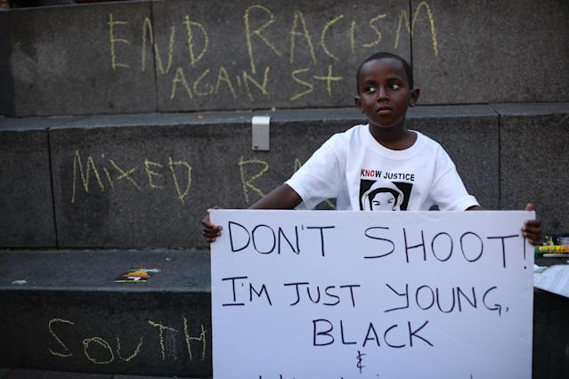 Abdul Kebbeh, 6, holds a sign at Westlake Park on Sunday, July 14, 2013 in downtown Seattle. Hundreds of people gathered at Westlake and marched to the United States Court House to protest the acquittal of George Zimmerman, the Florida man that shot and killed Trayvon Martin. (AP Photo/seattlepi.com, Joshua Trujillo)