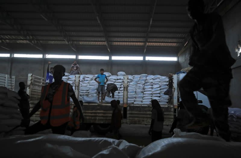 Ethiopian porters unload food aid bound for victims of war after a checkpoint leading to Tigray in Mai Tsebri town