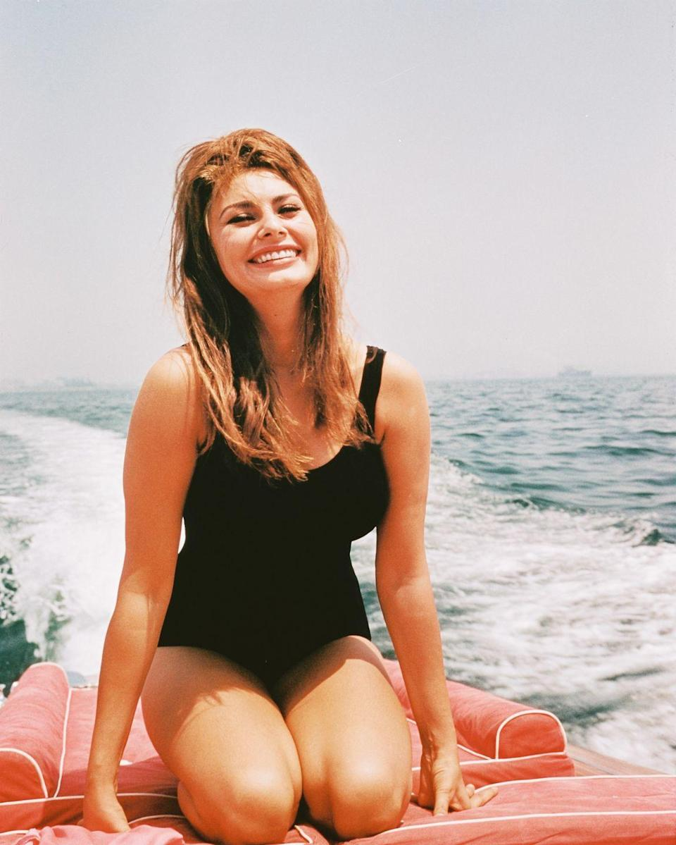 <p>Sophia Loren smiles from the stern of a motorboat. The Italian actress looks sun-kissed in a black one-piece bathing suit. </p>