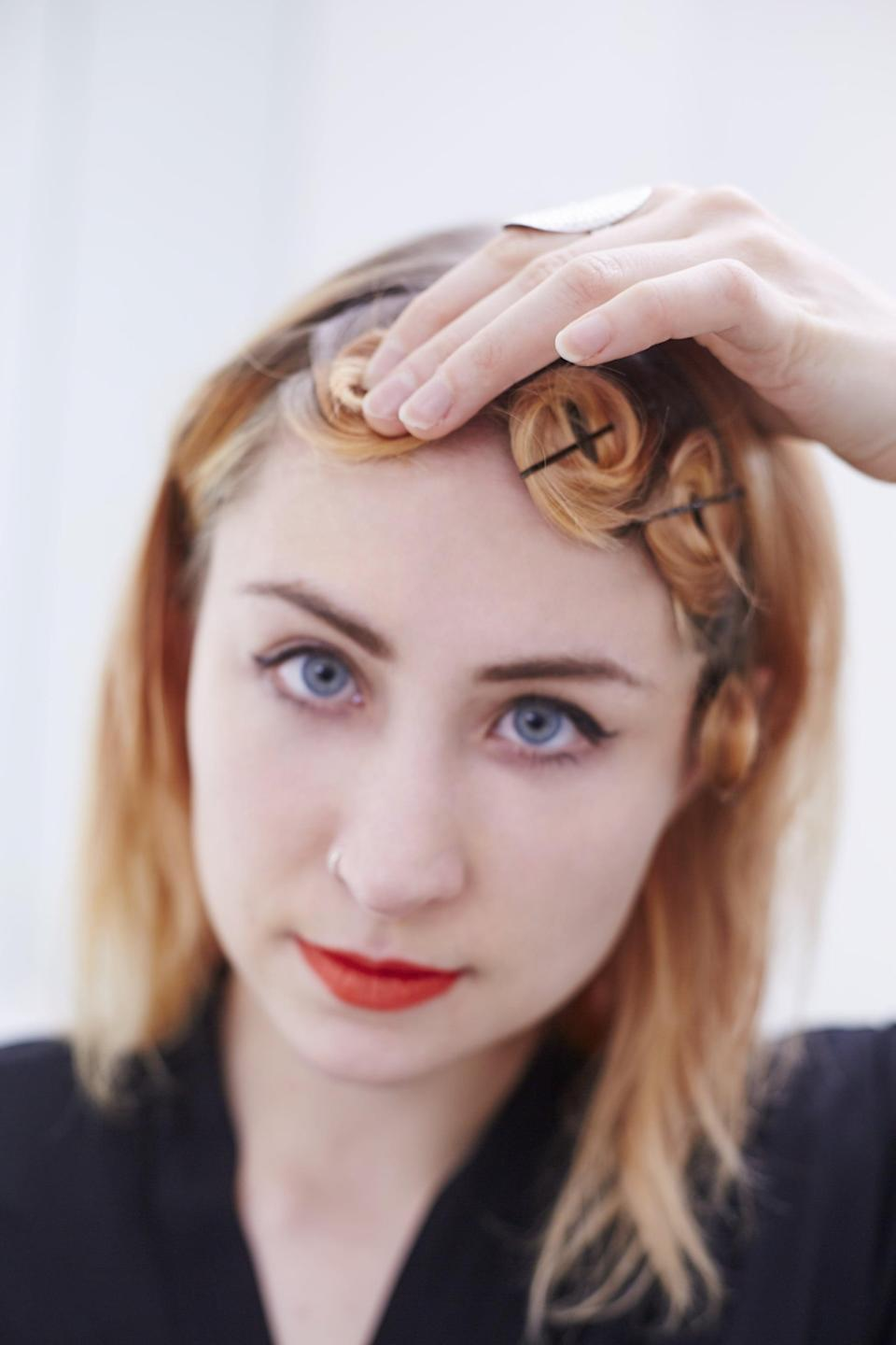 <p>Working one section at a time, roll the hair up from end to root. Once you have a pinwheel formed, secure it with a bobby pin or two.</p>