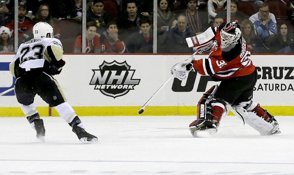 New Jersey Devils goalie Martin Brodeur, right, clears the puck out of danger as Pittsburgh Penguins right wing Chris Conner (23) skates in during the second period of an NHL hockey game, Tuesday, Dec. 31, 2013, in Newark, N.J. (AP Photo/Julio Cortez)