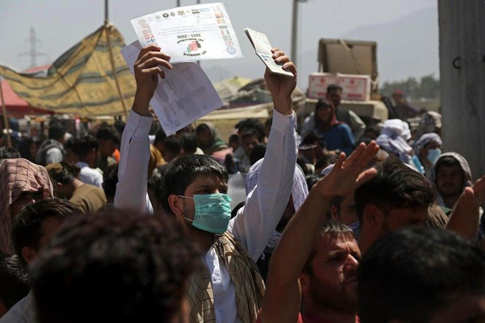 Hundreds of people gather near an evacuation control checkpoint on the perimeter of Kabul airport on Thursday (AP)