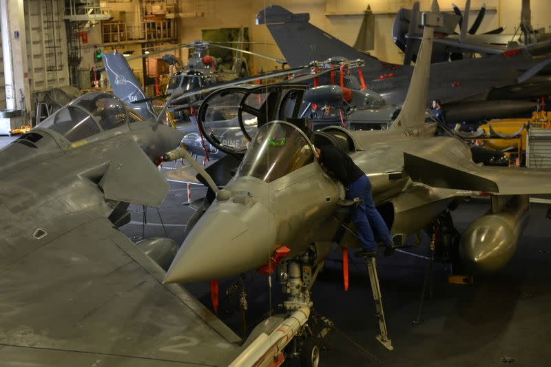 FILE PHOTO: An engineer works on a French Navy Rafale fighter jet, at the hangar bay of the Charles de Gaulle aircraft carrier, currently moored at the port of Limassol